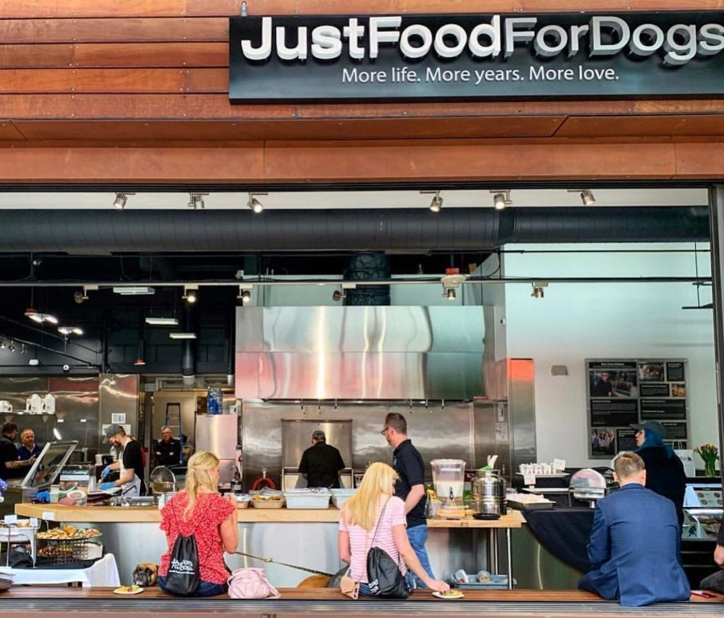 justfoodfordogs store front with people inside cooking