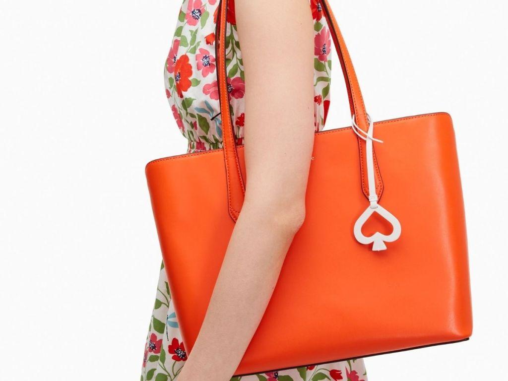 woman in flowery dress holding bright orange kate spade tote bag