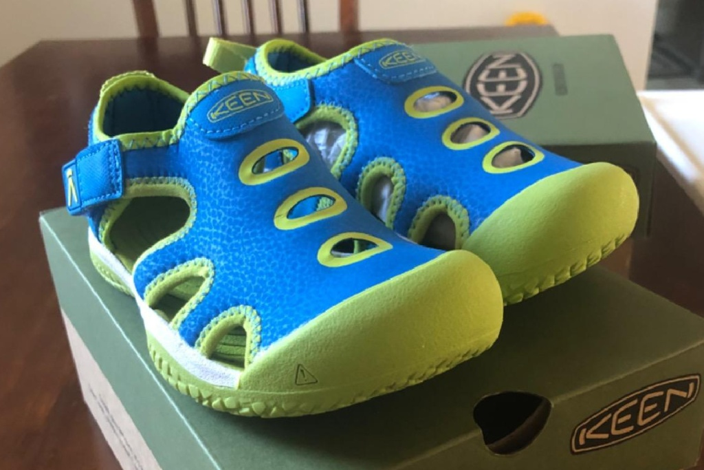 green and blue keen sandals on top of shoe box