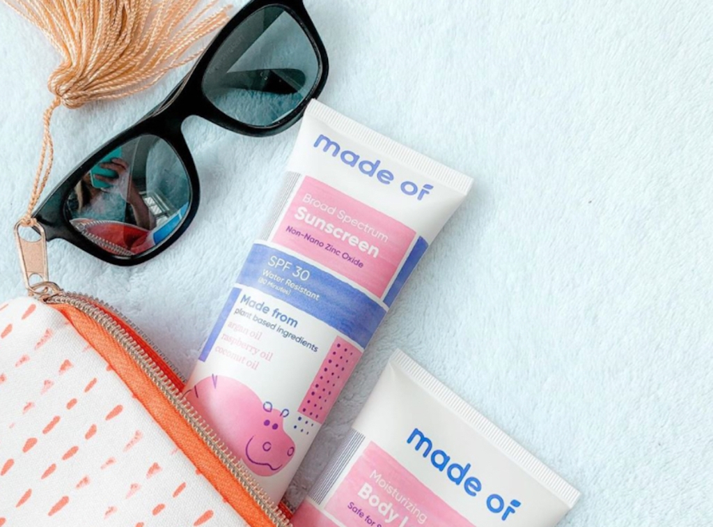 tube bottles of made of sunscreen lotion coming out of cosmetic bag with sunglasses