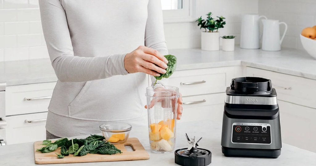 woman adding spinach to a blender cup