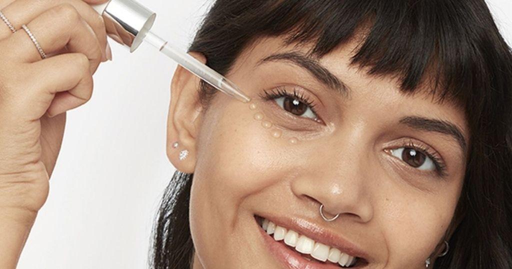 woman putting serum drops under eye