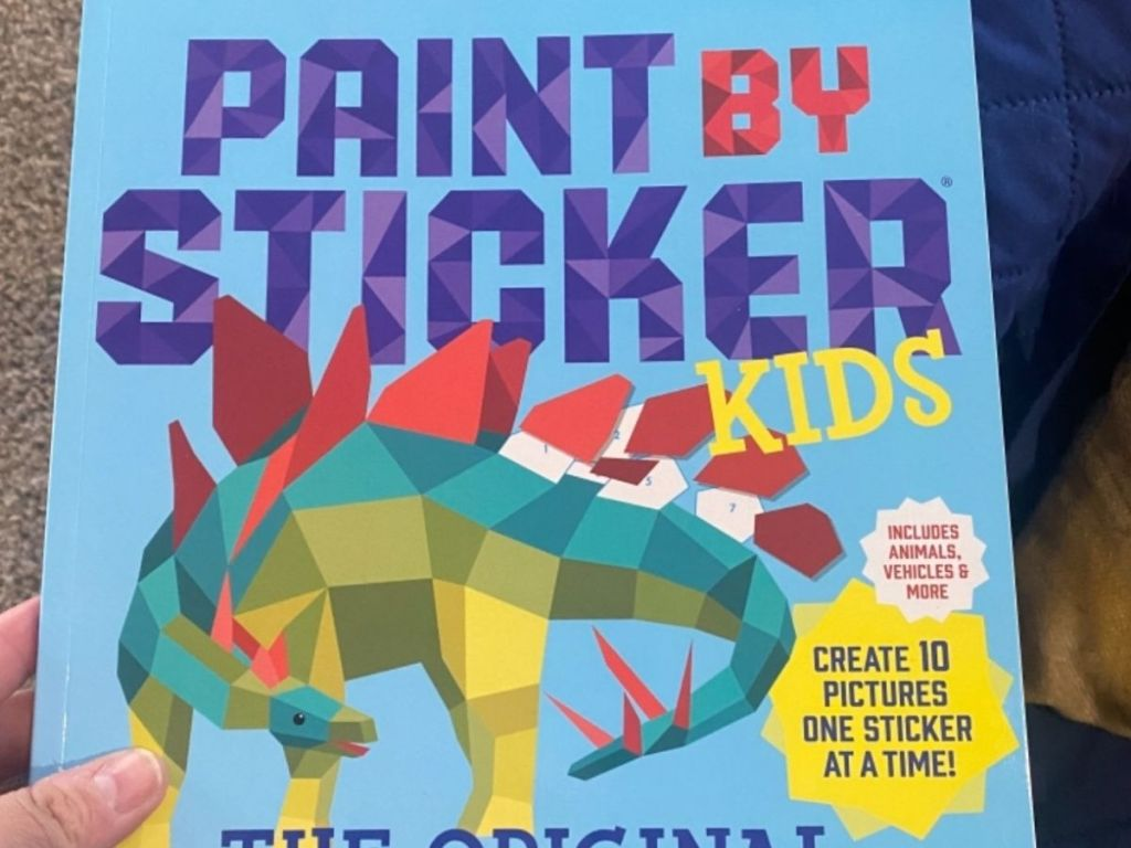 hand holding paint by sticker kids book