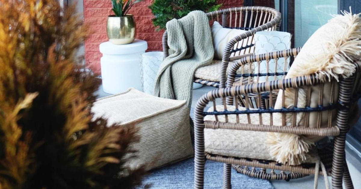 two patio chairs outside on a porch next to bushes