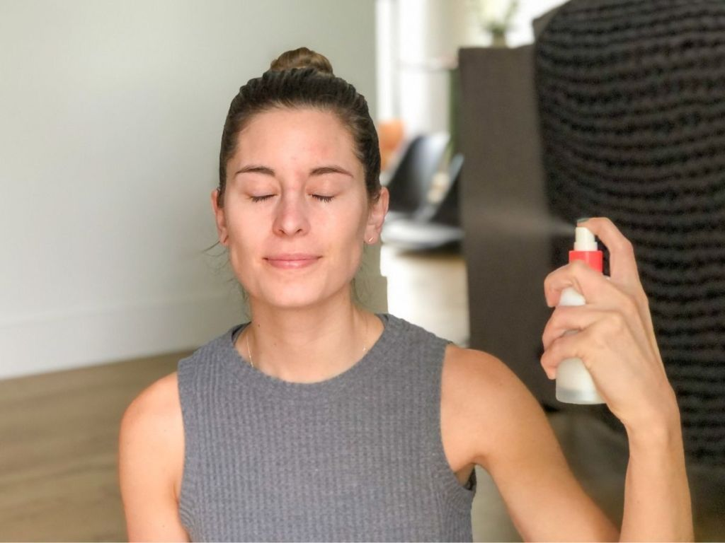 woman spraying mist on her face