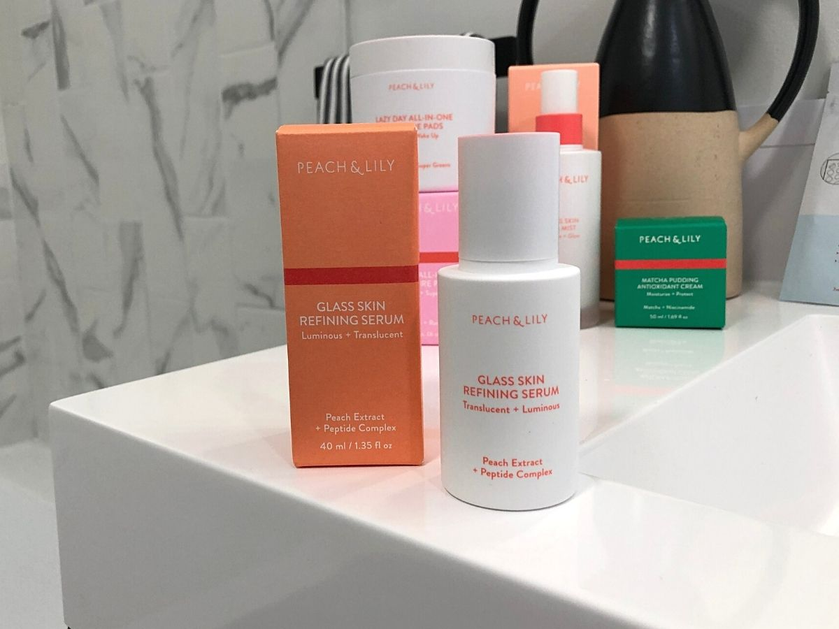 Peach & Lily glass skin refining serum bottle and box on sink