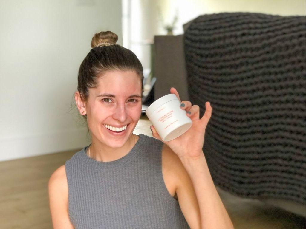 woman holding up white jar of moisturizing pads