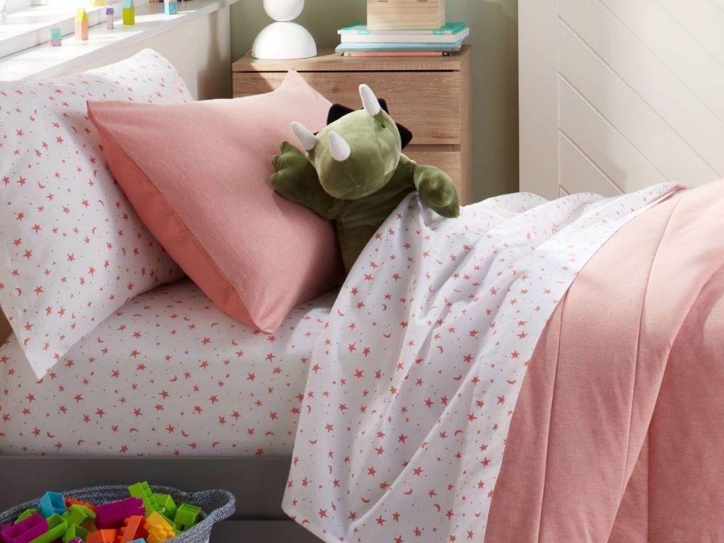 pink stars sheet on kids bed