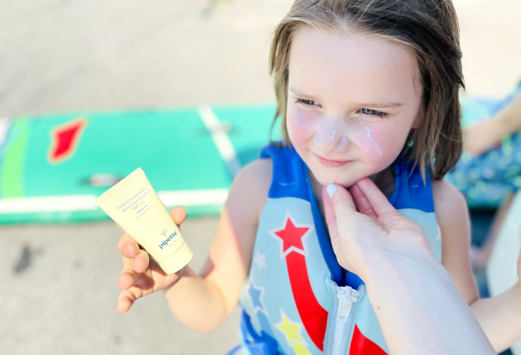 girl holding bottle of pipette kids sunscreen