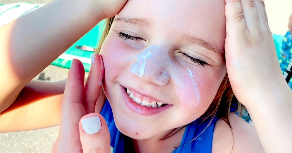 hand putting sunscreen on girls face