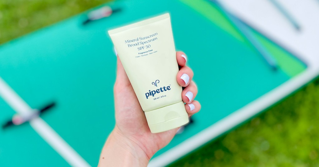 hand holding a bottle of pipette sunscreen