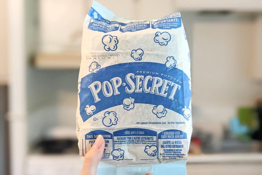 hand holding bag of popcorn