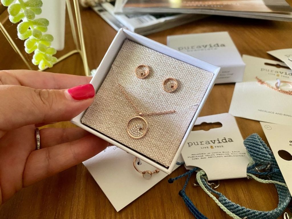 hand holding a box with a necklace and earrings