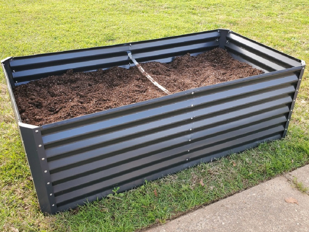 large steel box with soil sitting on grass