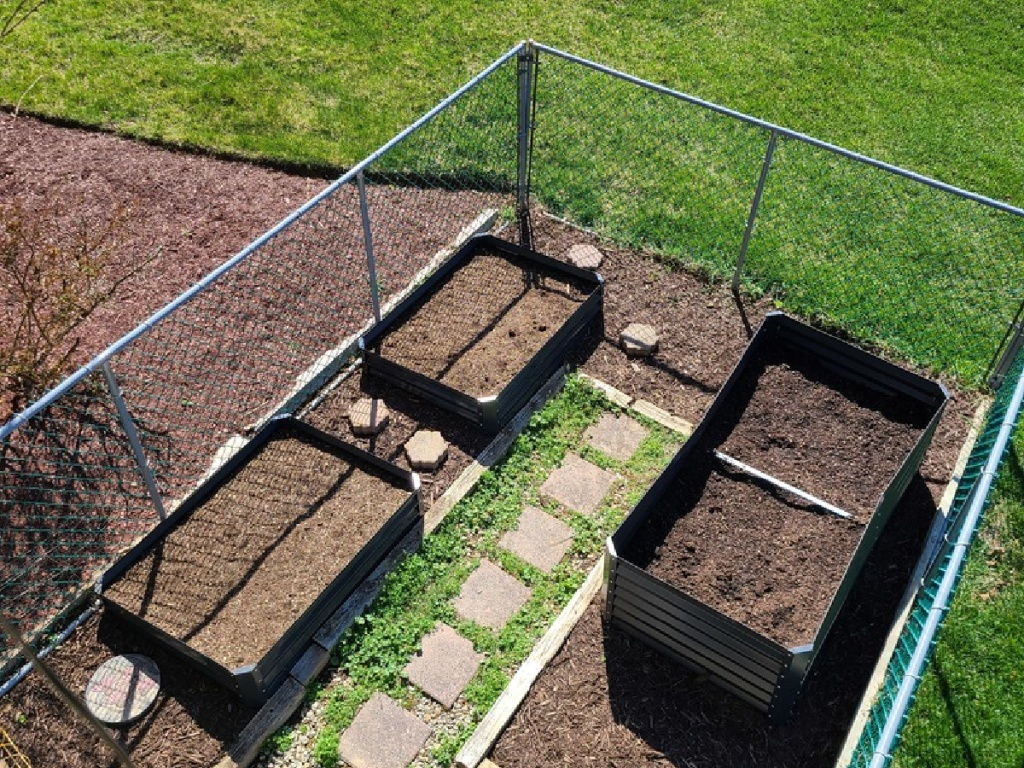 looking down on yard with raised garden beds in it