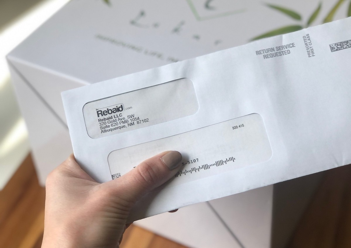 hand holding piece of mail from rebaid, Amazon rebate site