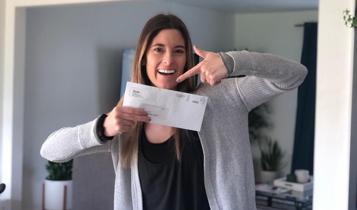 woman holding up envelope from rebaid, Amazon rebate site