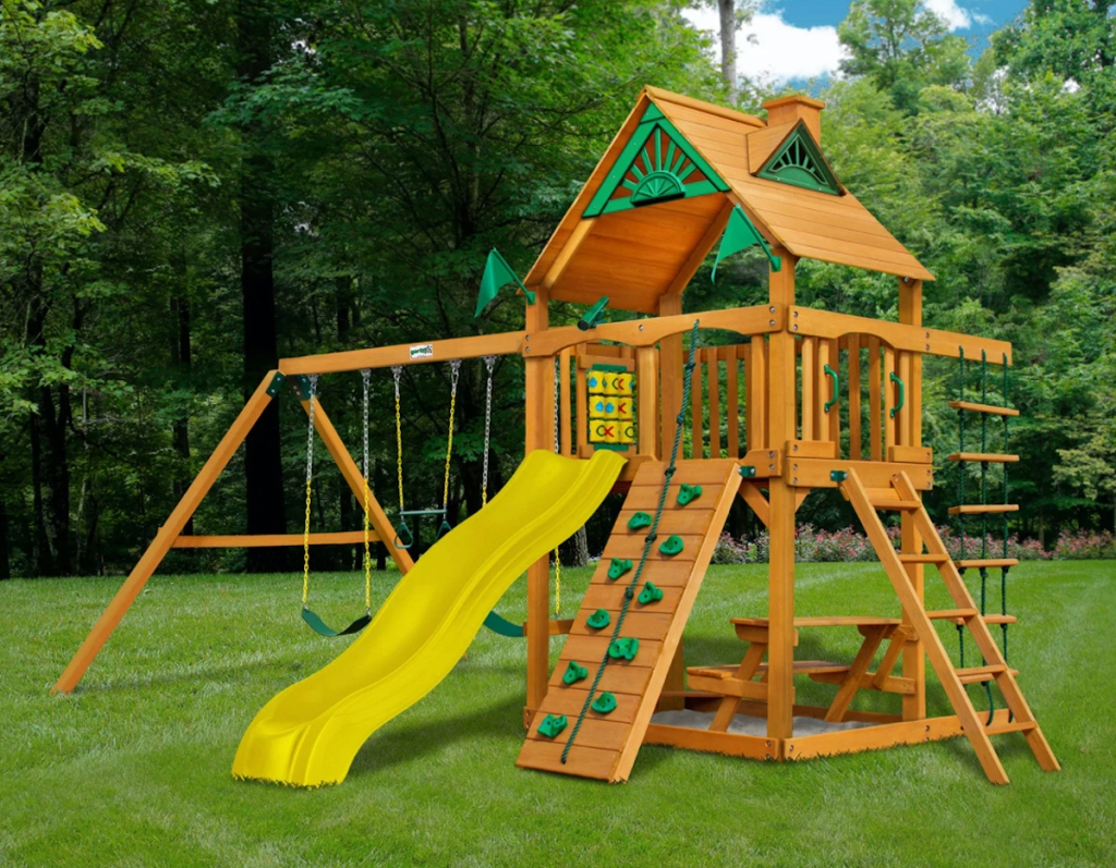 wooden play set with yellow slide and rock wall outside in grass