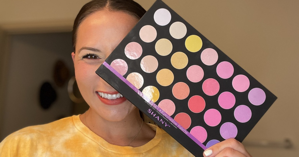 woman holding a large makeup palette in front of her face