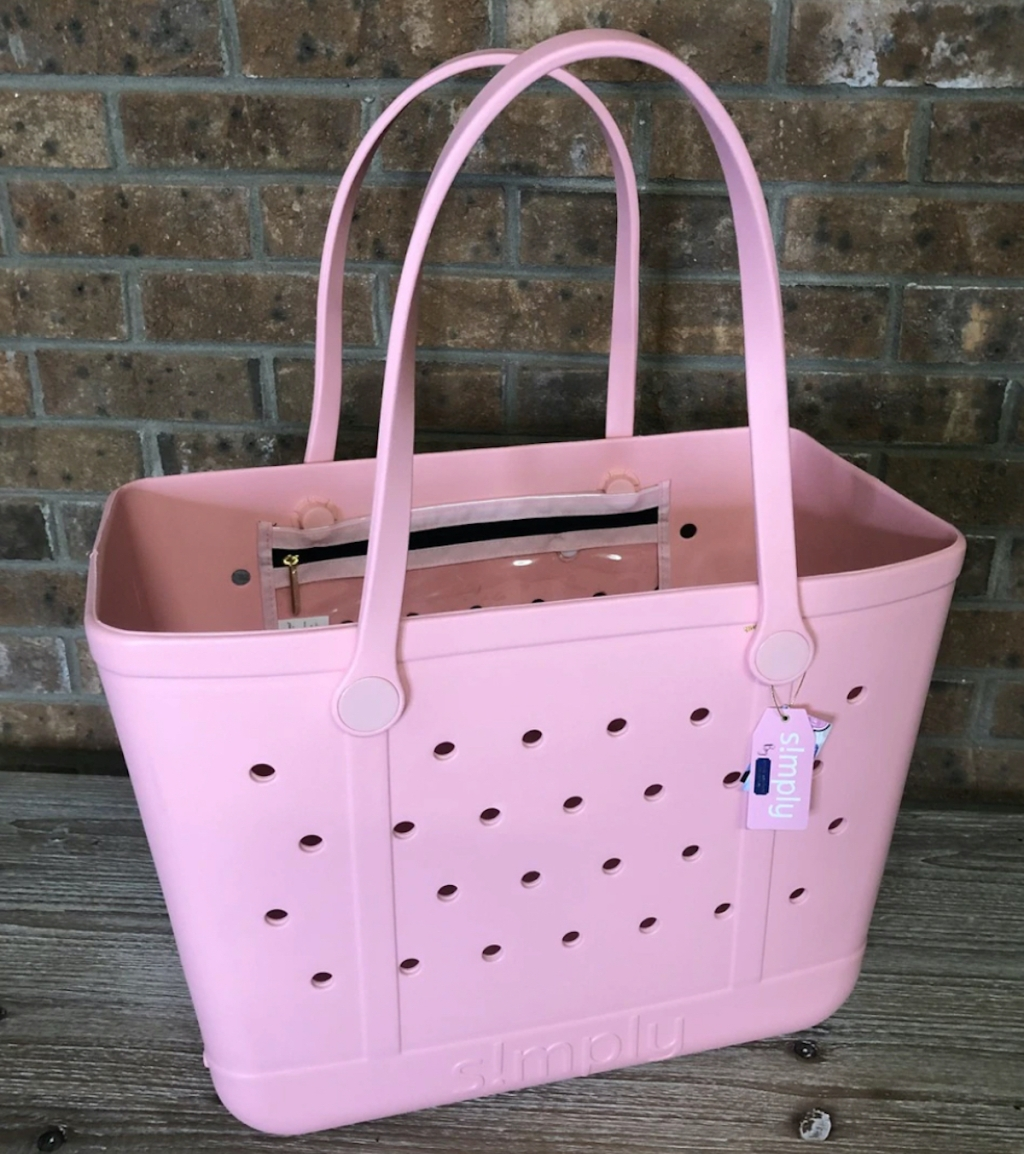 pink tote bag sitting in front of brick wall