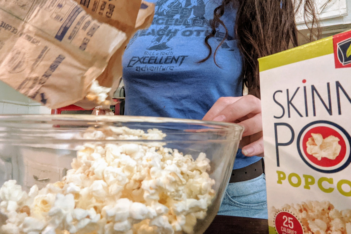woman pouring popcorn into a bowl