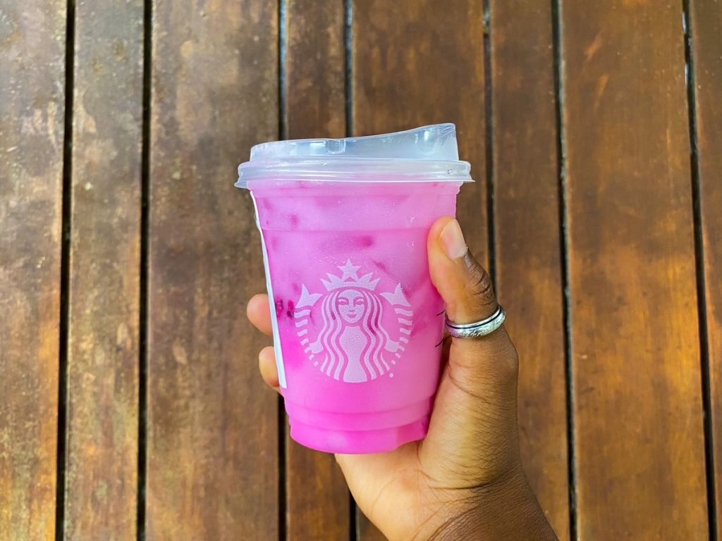 holding a pink iced Starbucks drink