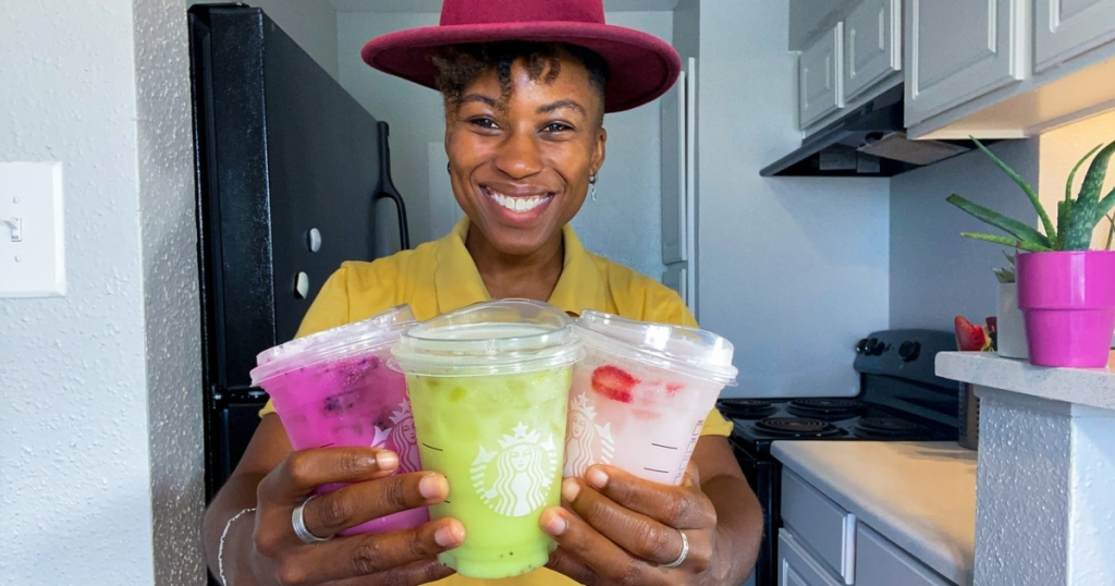 woman in hat holding 3 iced Starbucks drinks