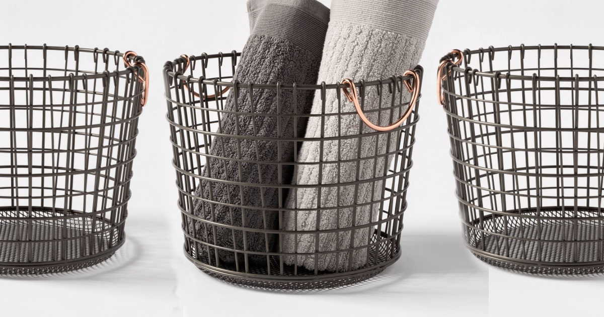 three wire baskets in a row, one with rolled up towels