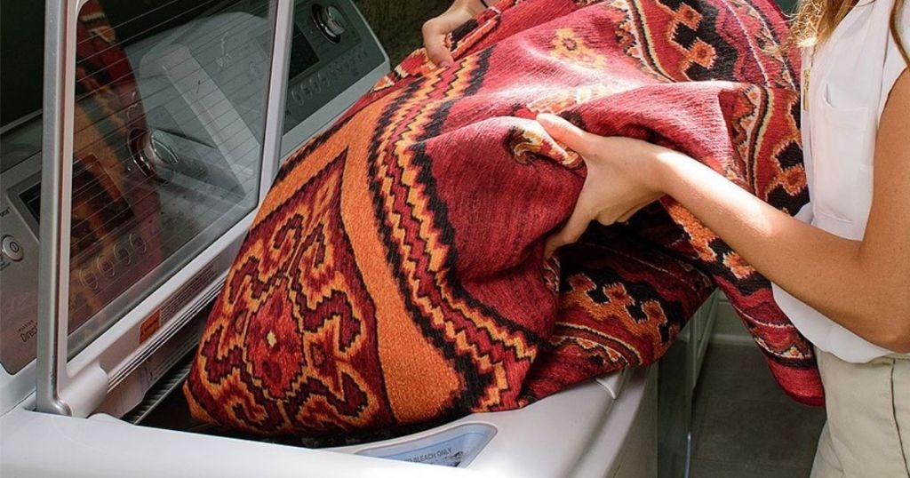 woman putting geometric rug in washer