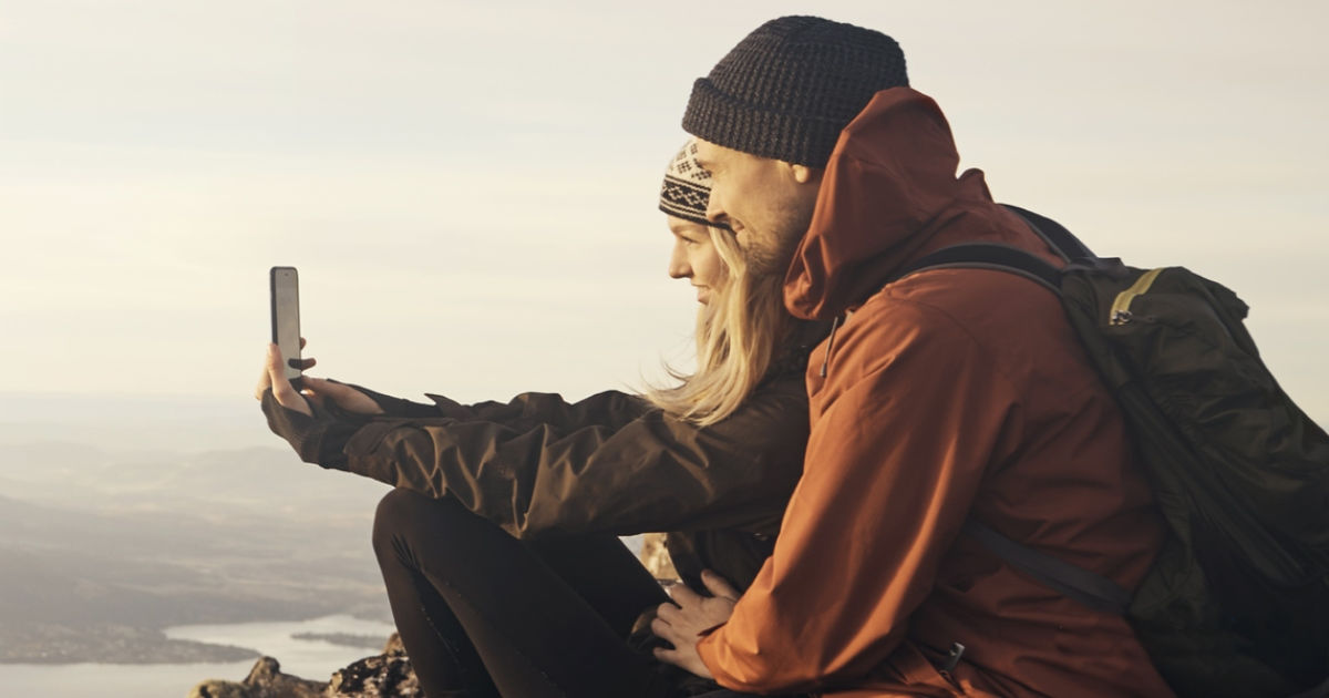 Man and woman taking selfie on mountain