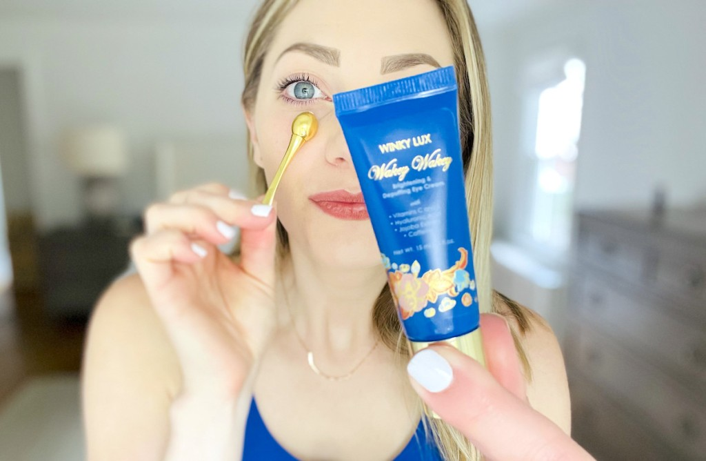 woman rolling gold tool under eye while holding up blue winky lux eye cream