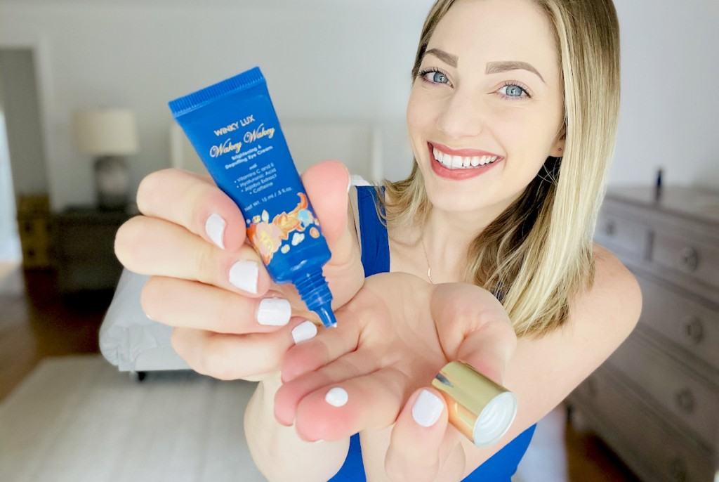 woman holding blue tube of winky lux eye cream
