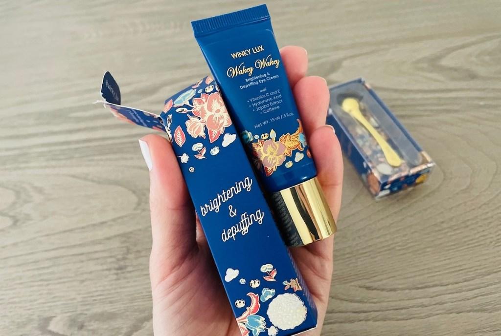 hand holding box and tube of eye cream