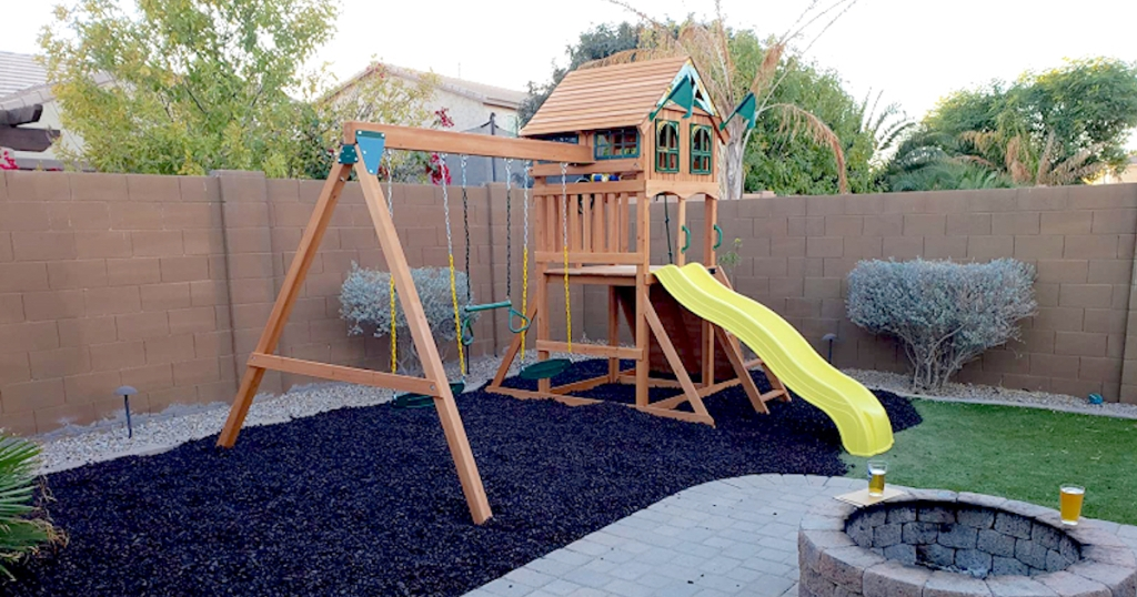 wooden playhouse swing set outside with yellow slide
