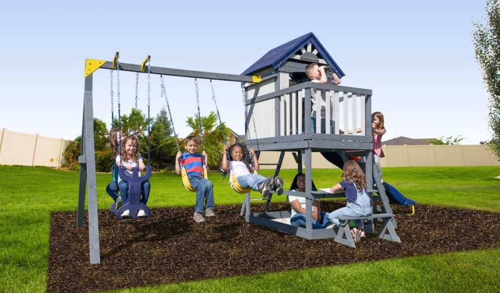 gray wooden swing set outside with kids playing on it