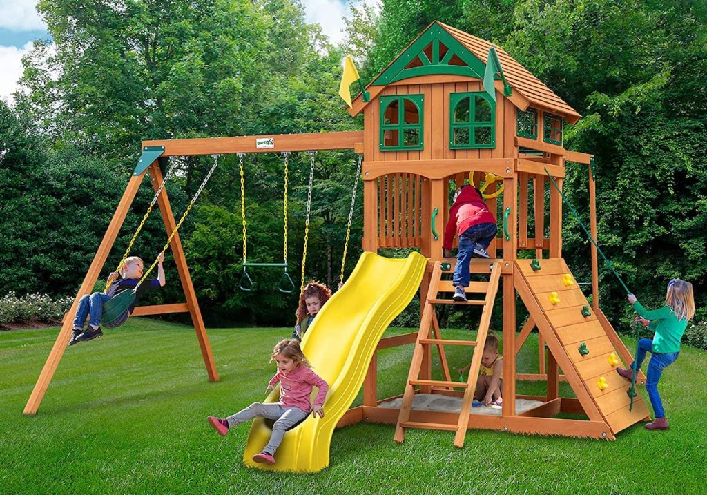 kids playing on wooden swing set outside