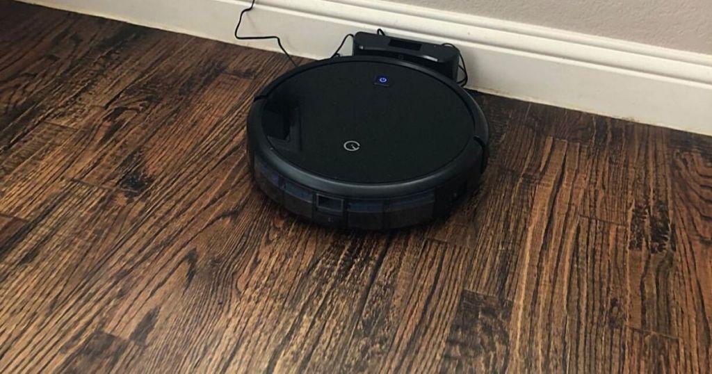 black robot vacuum cleaning wood floor