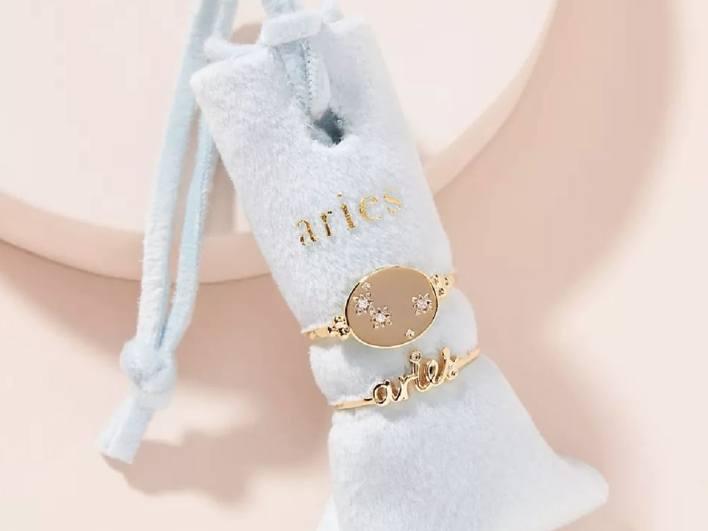 small ring pillow holding 2 gold rings