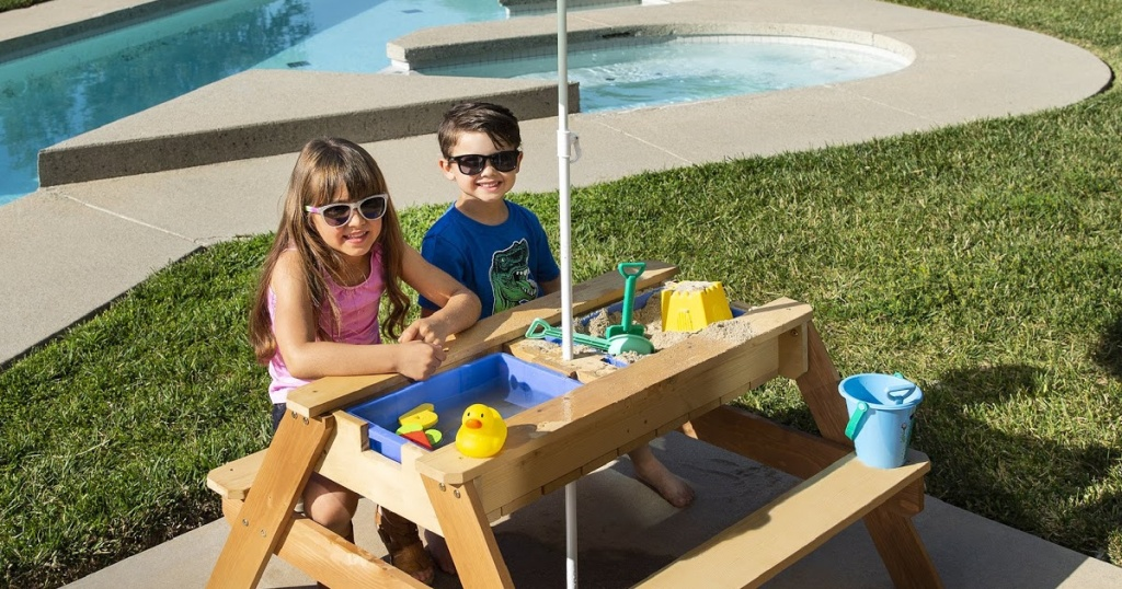 two kids sitting at an outdoor table