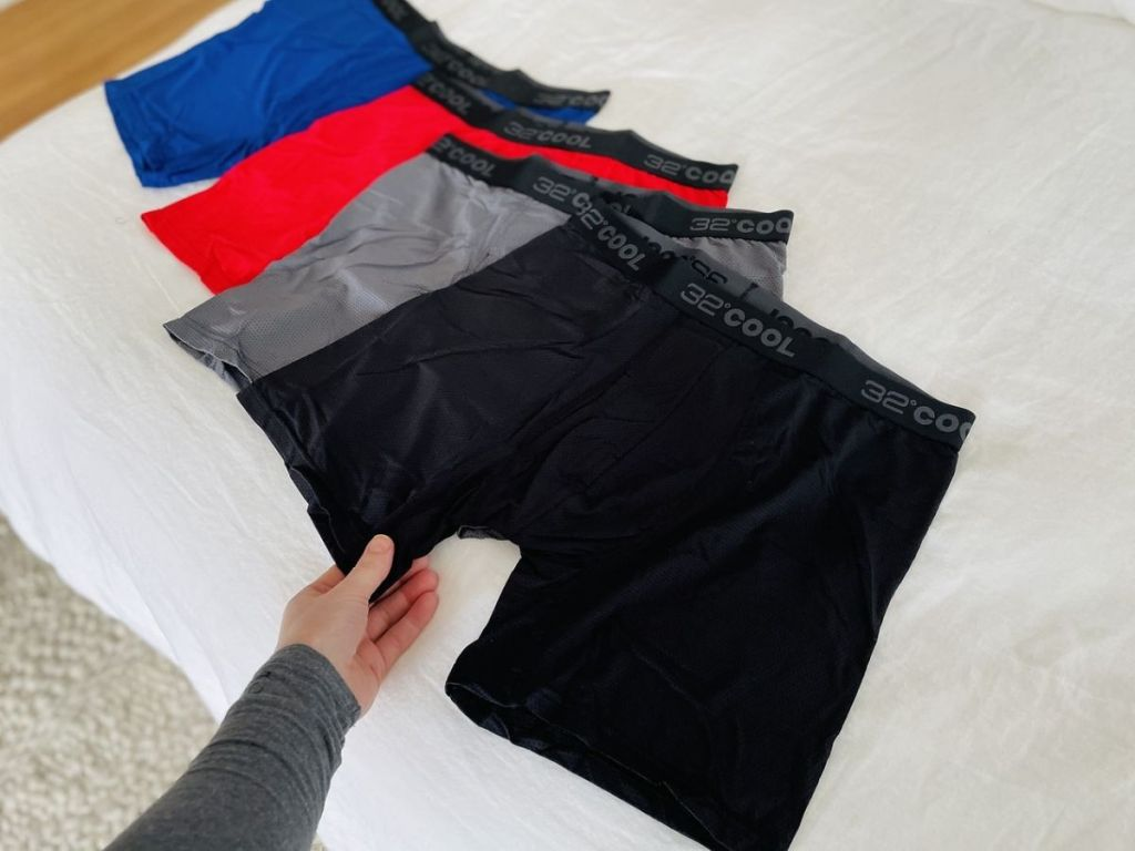 four pairs of men's boxer briefs on bed