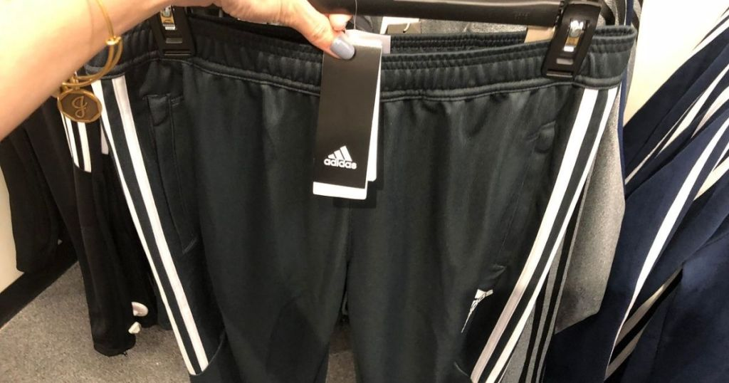 woman holding up hanger with men's Adidas shorts on it