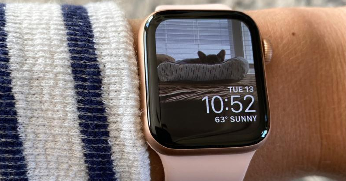 close up of a wrist with an apple watch reflecting a cat in a cat bed