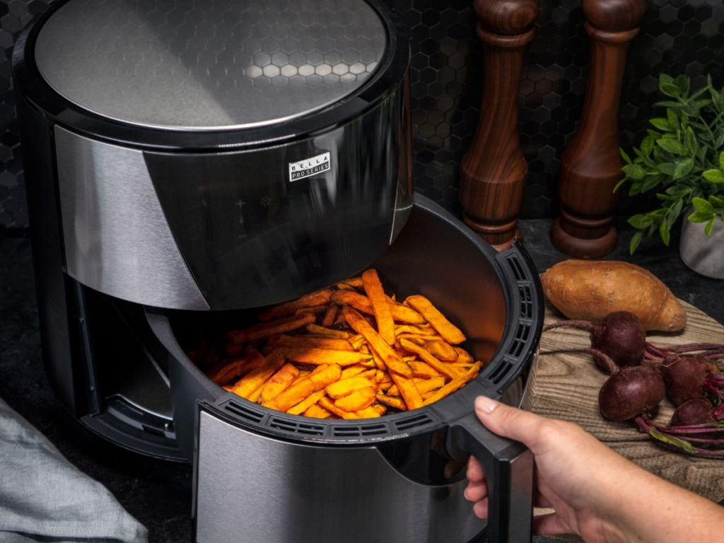 hand taking fries from bella air fryer