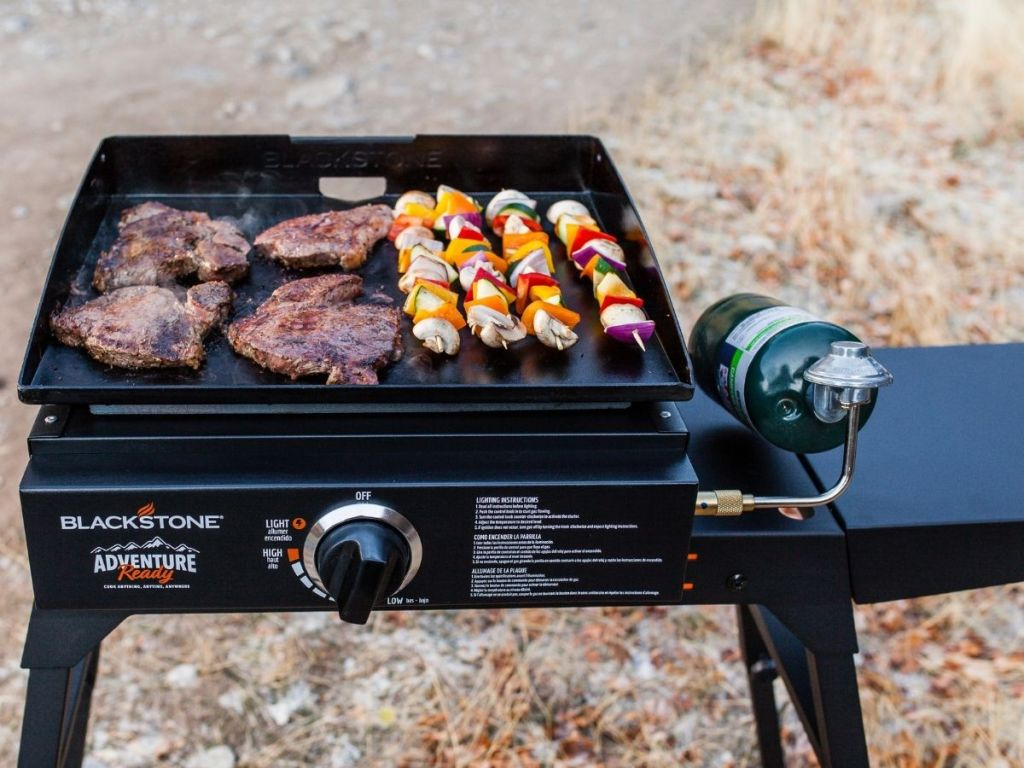 meat and kabobs on flat top grill