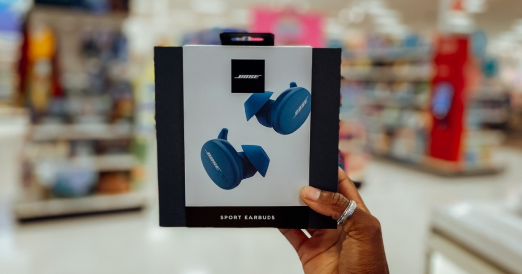Hand holding blue pair of earbuds