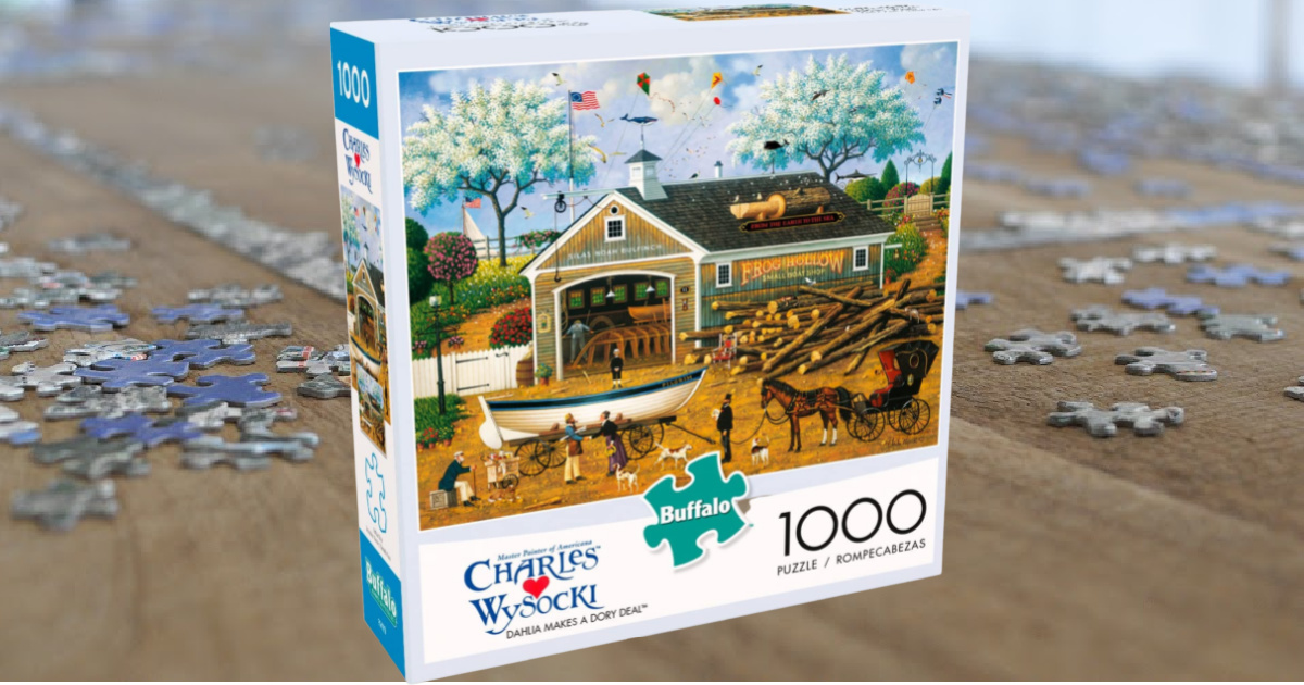 box containing a jigsaw puzzle featurine a barn and horses, on a table in front of a partially assembled puzzle