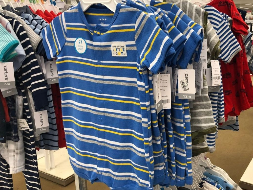 Carter's baby rompers hanging on rack at store