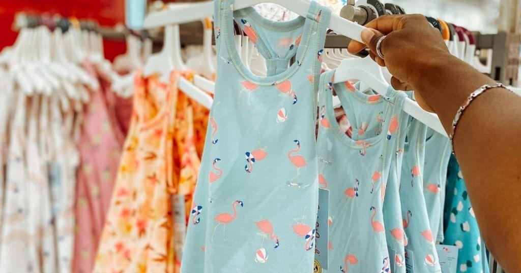 hand holding a dress on a hanger