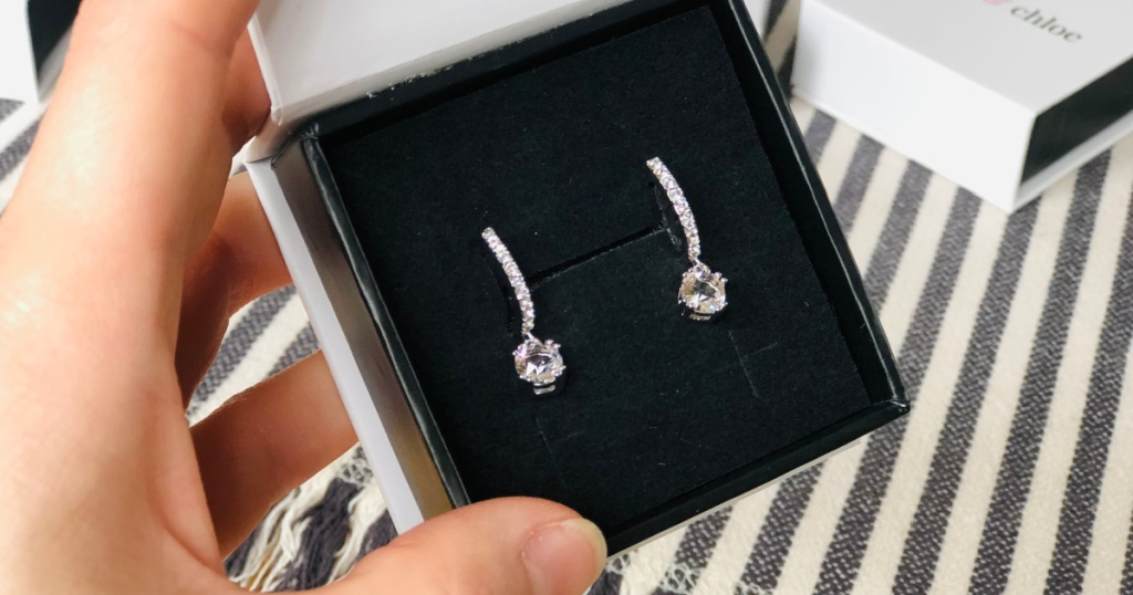 hand holding cate & chloe earrings in box