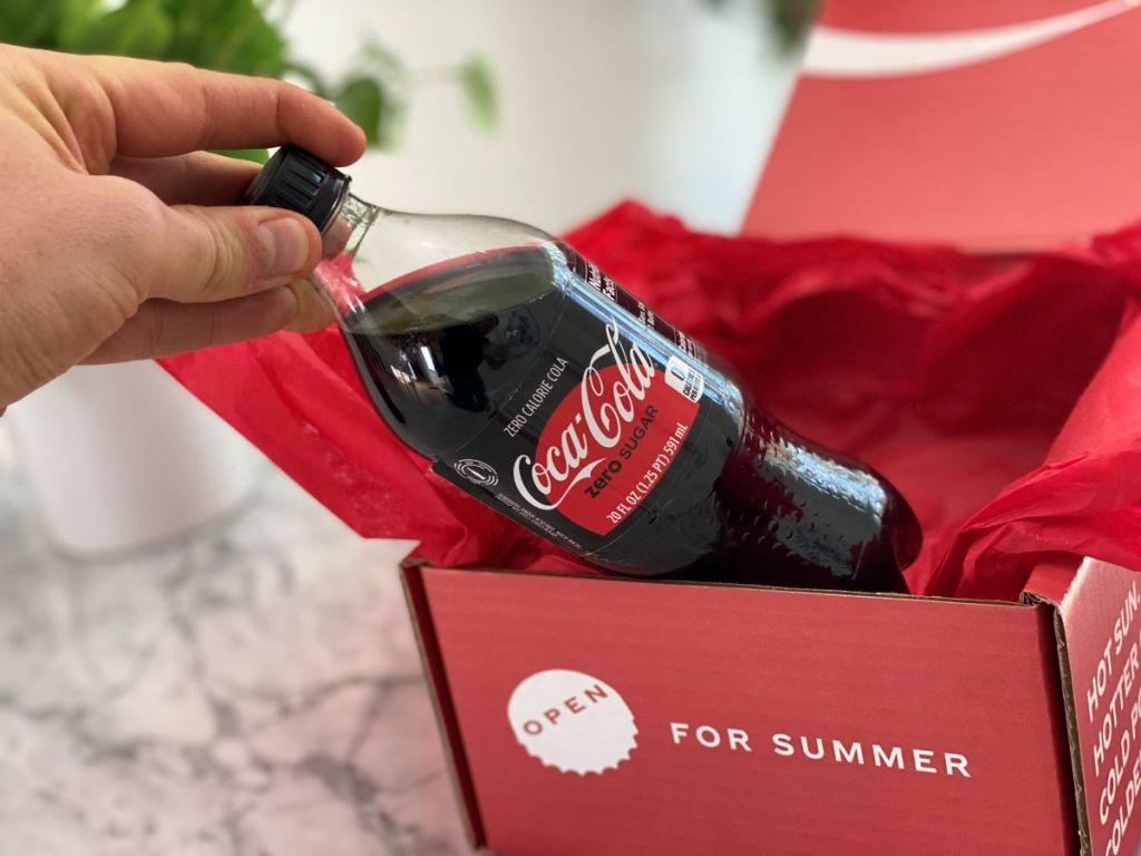 hand holding a bottle of Coke Zero